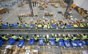 Employees sort boxes and parcels next to a conveyor belt at the logistic centre of a express delivery company, after the Singles Day online shopping festival, in Wuhan, Hubei province, China, November 12, 2015. On China's giant Singles Day internet shopping festival, the country's delivery firms are stretched so thin that they are looking for tie-ups, listings and new investors to husband their resources. E-commerce has been a huge boon to the logistics industry, but the ever-bigger Singles Day, run by leading online market company Alibaba Group Holding Ltd on Nov. 11 every year, exacerbates the industry's twin dilemmas of cut-throat competition and rising labor costs. With low barriers to entry, express couriers proliferated rapidly over the past decade to more than 8,000 firms, squeezing profit margins to about 5 percent, down from 30 percent 10 years ago, according to analysts. Picture taken November 12, 2015. REUTERS/Stringer CHINA OUT. NO COMMERCIAL OR EDITORIAL SALES IN CHINA  - RTS6QX7